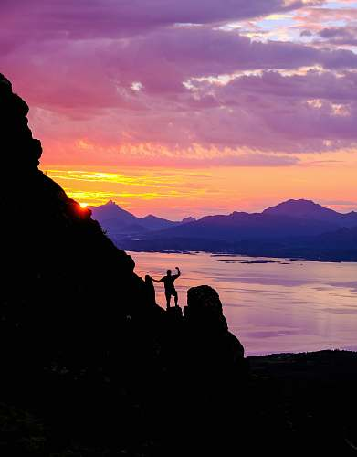 nature silhouette photography of person standing on cliff outdoors