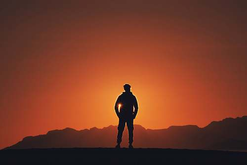 person silhouette photography of person standing on platform with mountain background during golden hour people