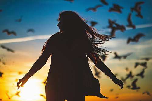 person silhouette photography of woman spreading her hands in front of flight of birds human