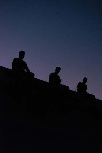 nature silhouette view of three men sitting on the roof grey
