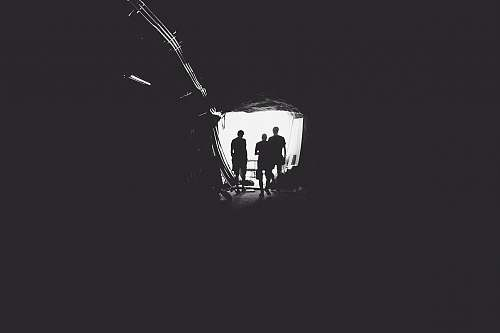 black-and-white three person standing in tunnel tunnel