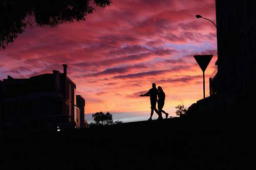 nature two persons walking near building sky