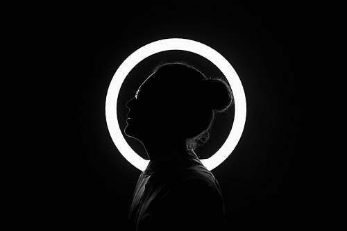 person woman standing beside halo light black-and-white