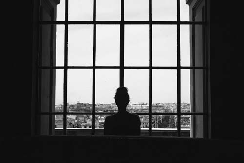 person woman standing in front glass window black-and-white