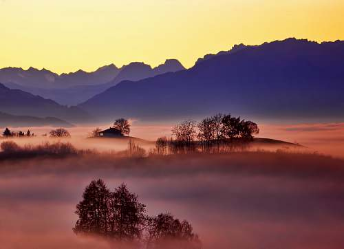 sunset aerial photo of foggy trees and mountains sunrise