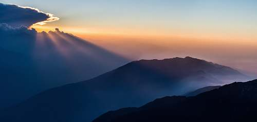 sunset aerial view photography of mountain under clear blue sky during daytime nature