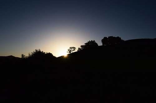 sunset silhouette photo of mountain nature