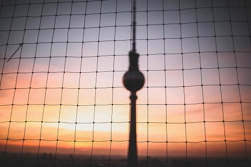 berlin silhouette photo of hanging decor behind chain link fence at golden hour germany