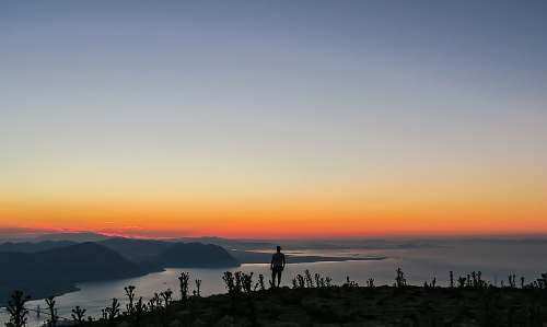 sunrise silhouette photo of man standing on mountain nature
