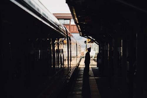 train man standing near train in subway during daytime train station