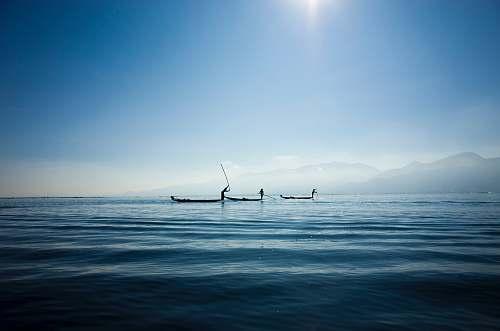blue calm body water under blue sky fishing
