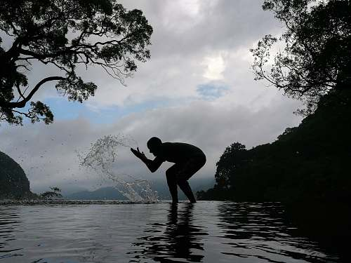 human silhouette of person splashing water person