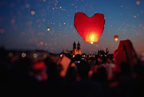 people crowd of people flying heart lanterns in the sky ball