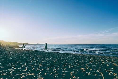 coast two person walking on seashore during daytime ocean