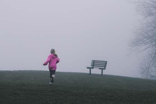 child girl running near black bench running