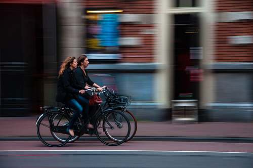 bicycle time lapse photography of two person riding bicycle transportation