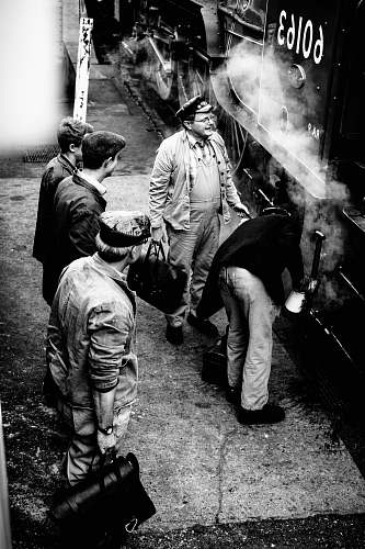 person grayscale photo of men standing beside 60163 train people