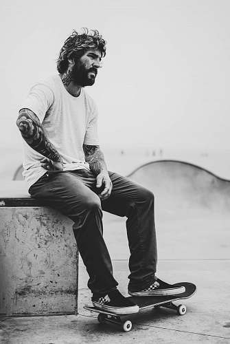 human grayscale photography of man sitting on bench while his feet on skateboard people