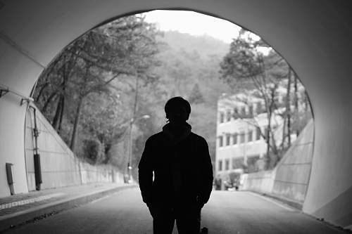 human grayscale photography of man standing in tunnel people