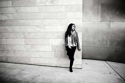 human grayscale photography of woman leaning on wall people