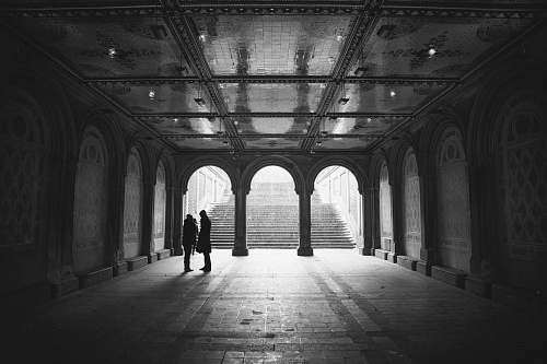 building grayscale two people standing on hallway arch