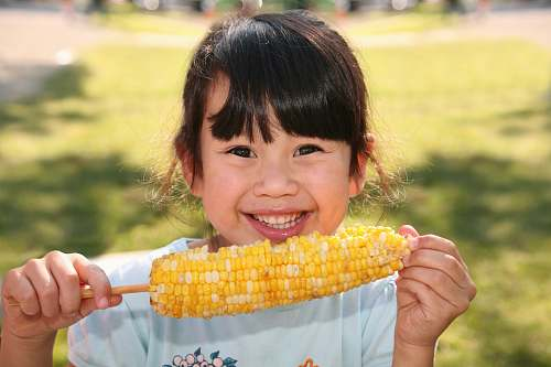 grain smiling girl holding cooked corn during daytime plant