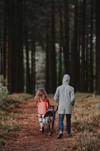 people black dog between man and girl walking person