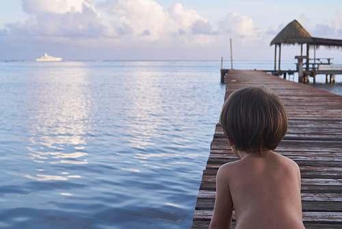 person boy kneeling on wooden dock people