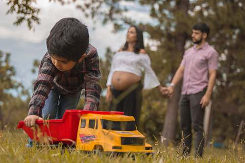 people boy playing red and yellow truck on grass field person