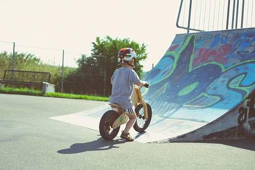 person boy riding brown bike people