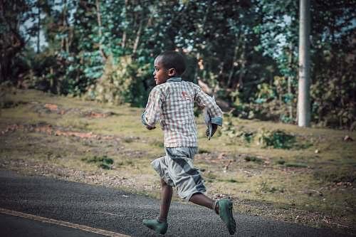person boy running on asphalt road near grass field people
