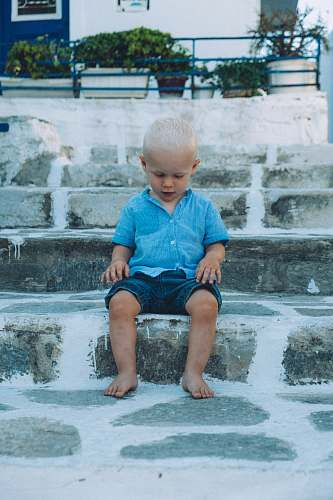 person boy sitting on gray concrete stair people