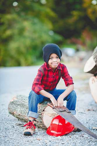 people boy sitting on log holding handsaw over red hard hat person
