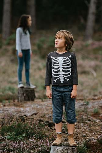 people boy wearing black and white skeleton-printed crew-neck sweatshirt while standing on log person