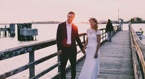 people bride and groom standing on wooden dock near body of water person