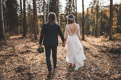 people bride and groom walking on leaves covered ground in woods during day person