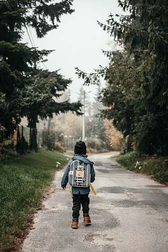 people child carrying backpack while standing near green trees and plants person
