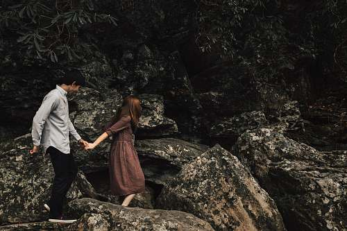 people couple standing on rocky cliff person