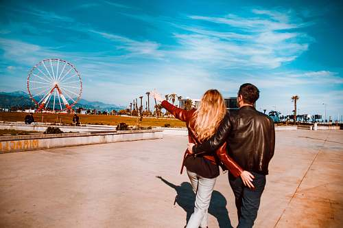 people couple walking girl pointing red ferris wheel under blue sky and white clouds person