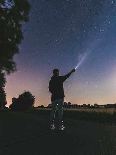 people force photography standing man using flashlight at star person