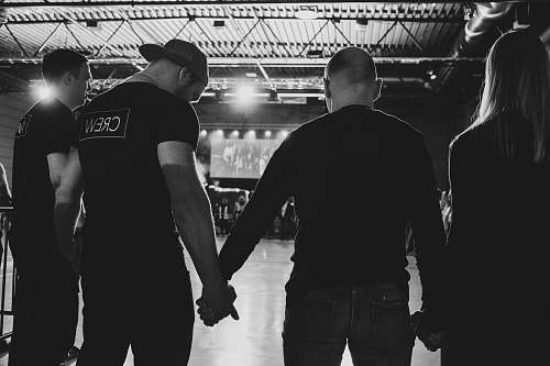people four unknown person standing while holding hands black-and-white