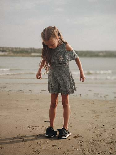 people girl wearing gray dress standing on shore person