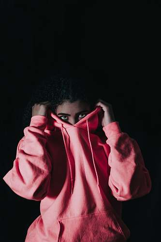 people girl wearing pink pullover hoodie covering her nose person