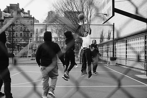 people grayscale photo of group of men playing street basketball black-and-white