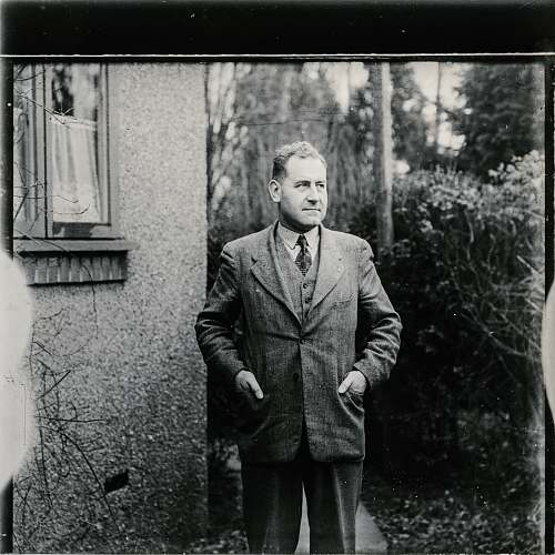 people grayscale photo of man wearing suit standing beside wall with mirror black-and-white