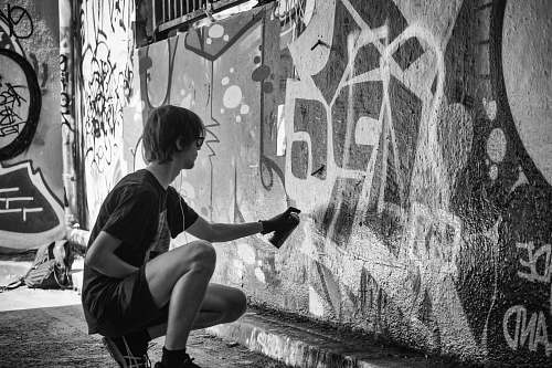 people grayscale photography of man vandalize the wall during daytime black-and-white