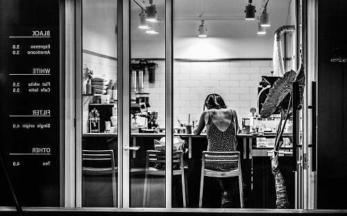 people grayscale photography of woman inside cafe black-and-white