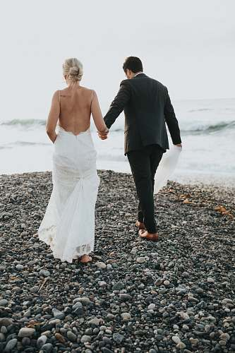 people groom and bride walking on stone near body of water person