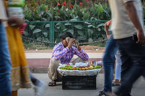 people male vegetable vendor at street during daytime person