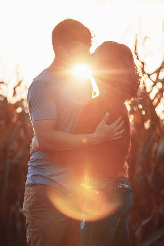 people man and woman kissing during golden hour person